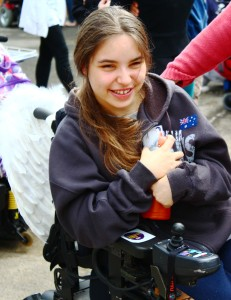 A teenage girl in a motorised wheelchair with a smile on her face.