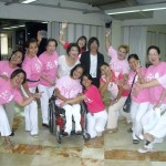 Happy women posing with a lady in a wheelchair (all wearing pink t-shirts)